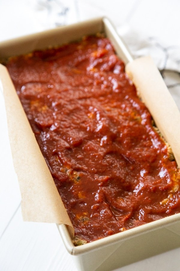 An unbaked lentil loaf in a bread pan with BBQ sauce spread on top.