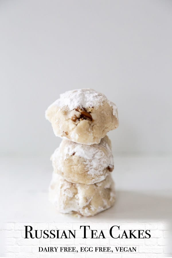 A PInterest pin for vegan Russian Tea Cakes with a picture of the cookies stacked on top of each other.