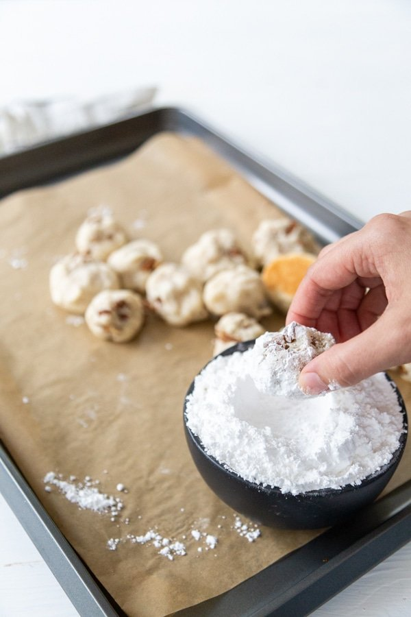 A hand rolling a Russian Tea Cake cookie in a bowl of powdered sugar.