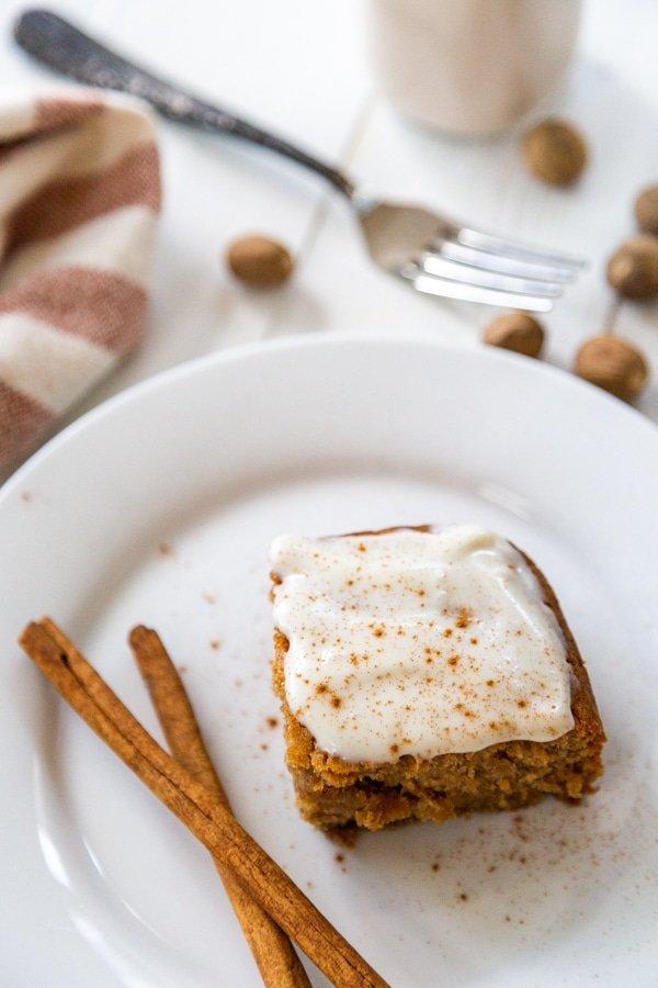 A slice of cake with cream cheese frosting on a white plate with 2 cinnamon sticks.