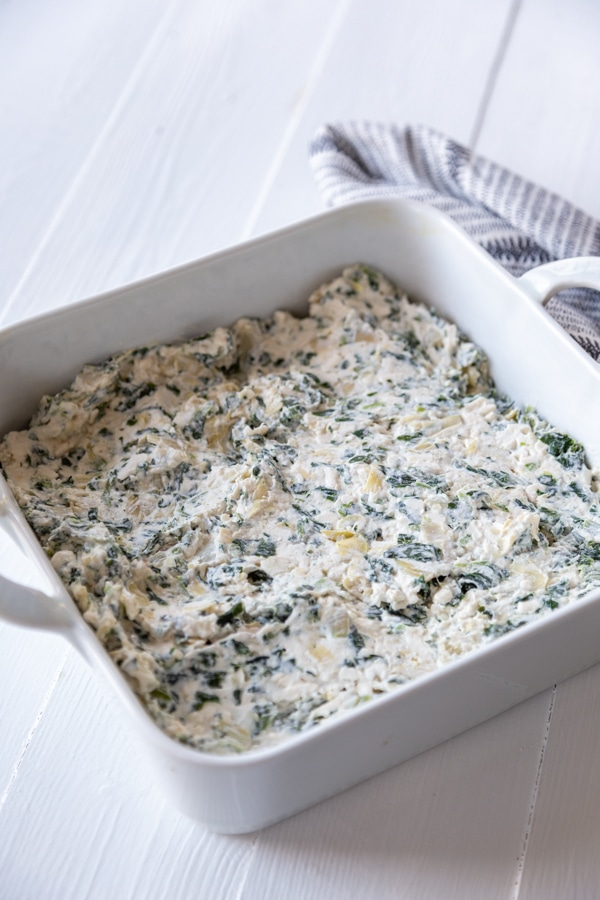 A square white baking dish with spinach artichoke dip.