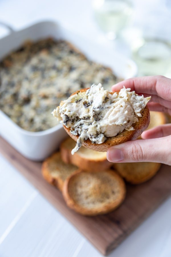 A hand holding toast with spinach artichoke dip spread on top, and a board with a pan of the dip and toast.