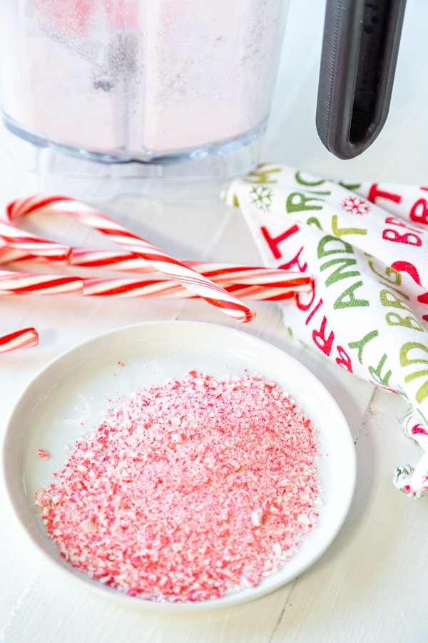 A white plate with ground candy cane and candy canes and a blender next to the plate.