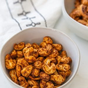 2 bowls of roasted spicy nuts and a white and black towel on a white table.