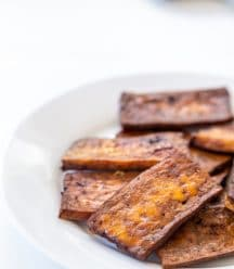 A stack of vegan tofu bacon on a white plate.