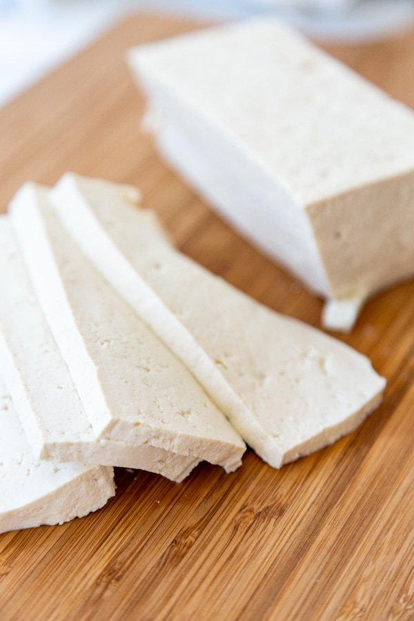 A block of firm tofu sliced into strips.