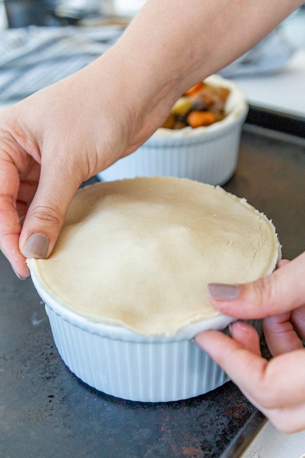 2 hands putting pie dough on top of a white bowl filled with vegetable stew.