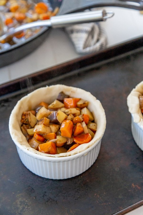 A white bowl lined with pie dough filled with vegetable stew.