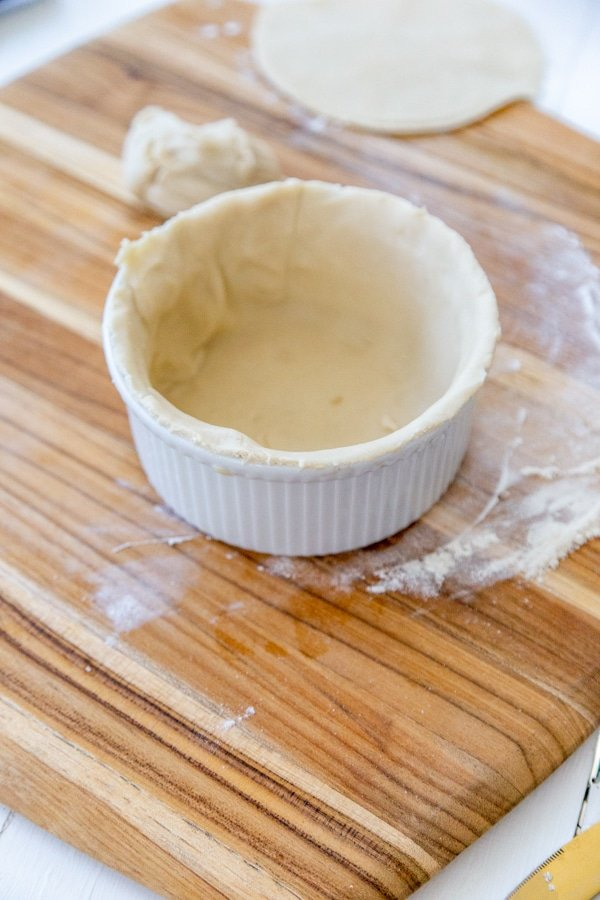 A white bowl on a wood board with pie crust lining the bottom and sides of the bowl.