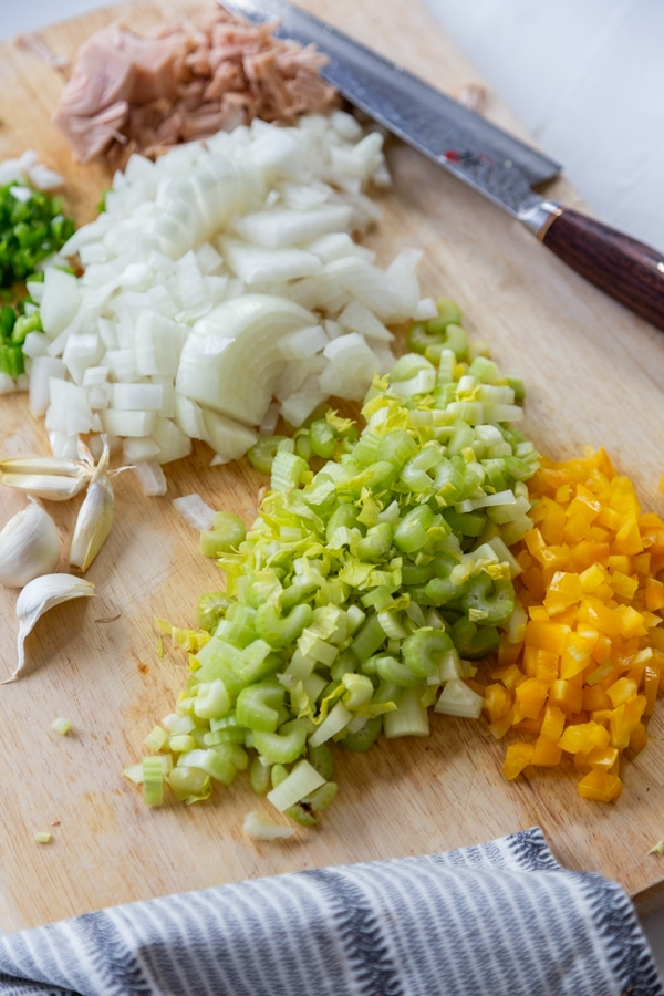 Chopped celery, onion, and bell pepper on a wood cutting board.