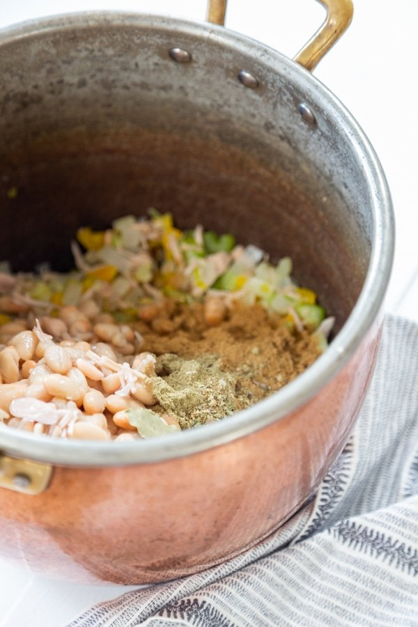 A copper pot with sauteed veggies and spices.