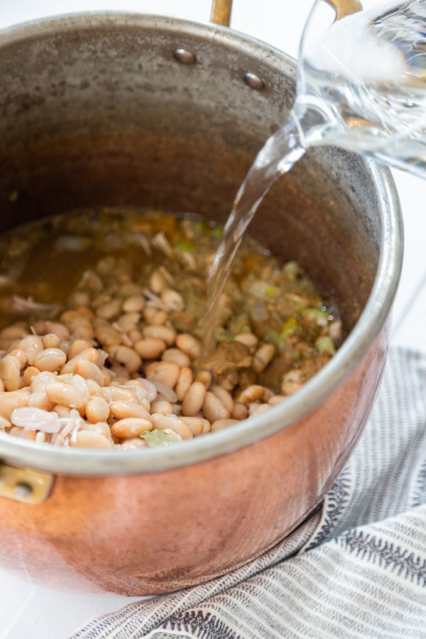 A copper pot with sauteed veggies, white beans, broth, and water being poured into the pot.