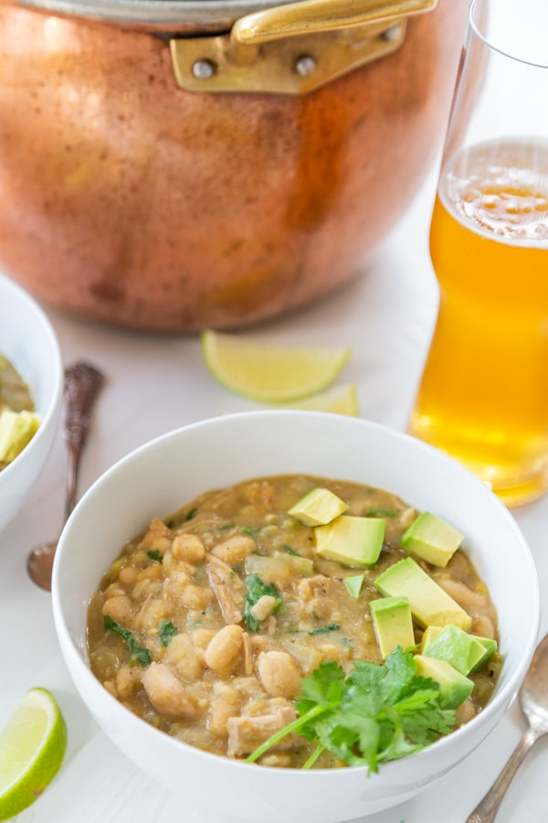 A white bowl with white chili and a copper pot and a glass of beer behind it.