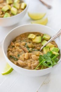 A bowl of white bean chili with avocado and cilantro on top and a spoon in the bowl.