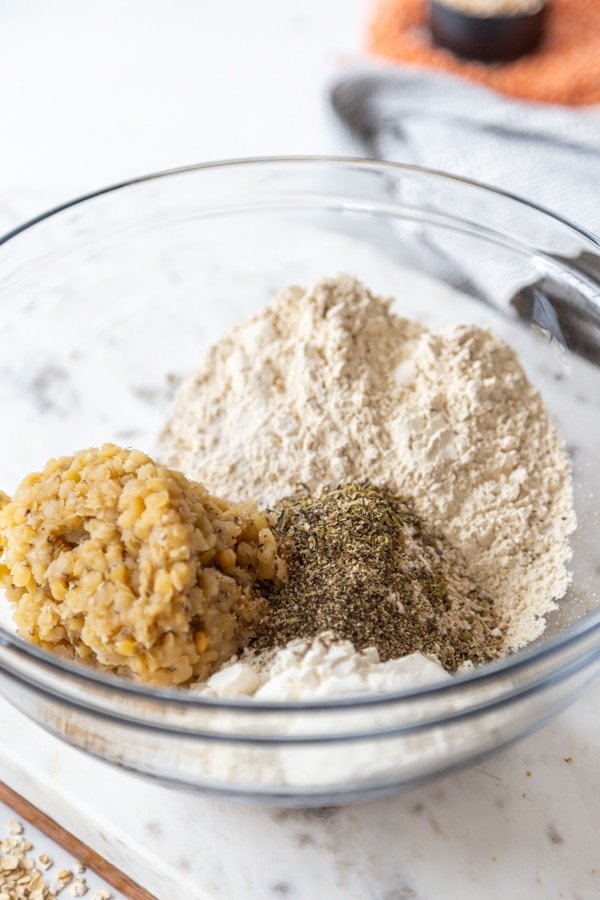 A clear mixing bowl with flour and spices.