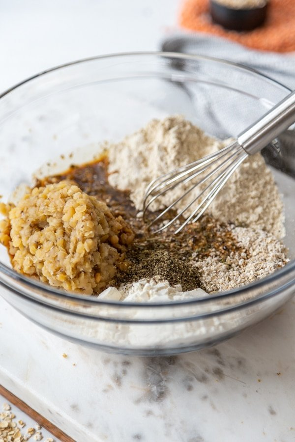 A whisk mixing flour, lentils, and spices.