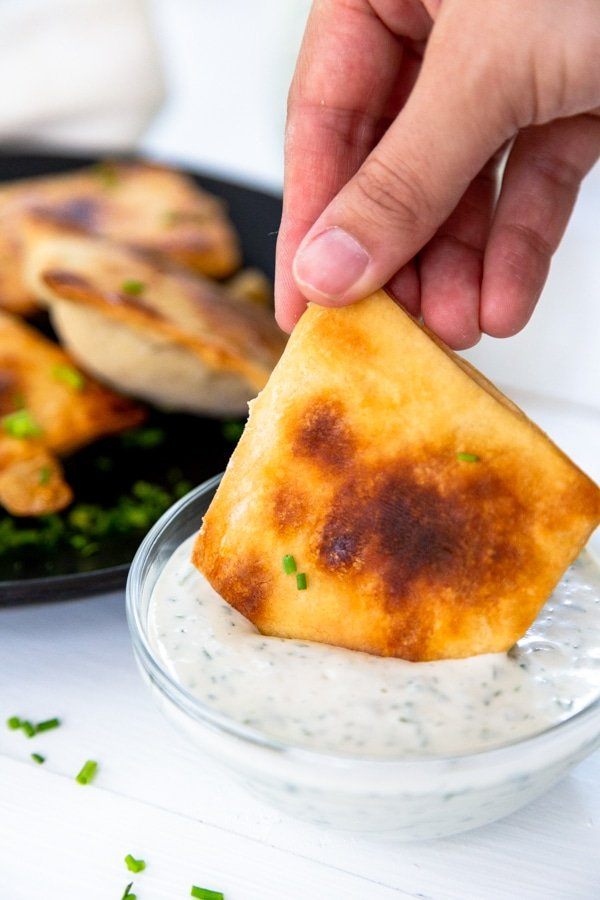 A hand dipping a calzone into a glass bowl of ranch dressing.
