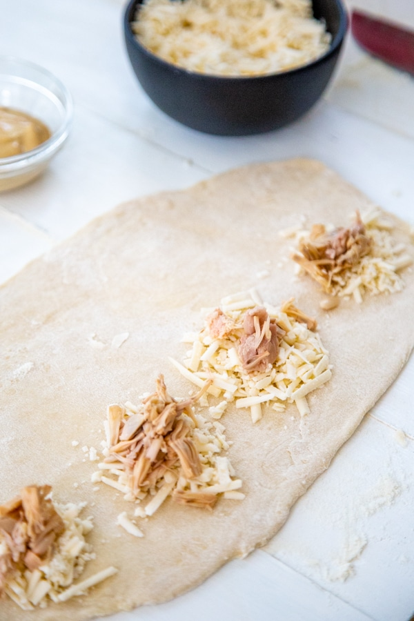 Dough rolled out into a rectangle with dollops of cheese and jackfruit.