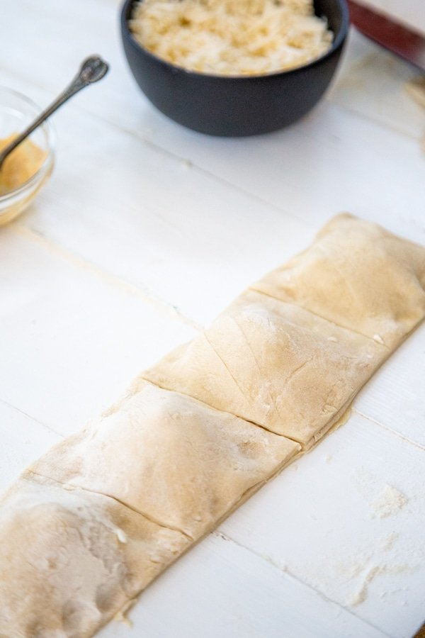 A row of unbaked square calzones.