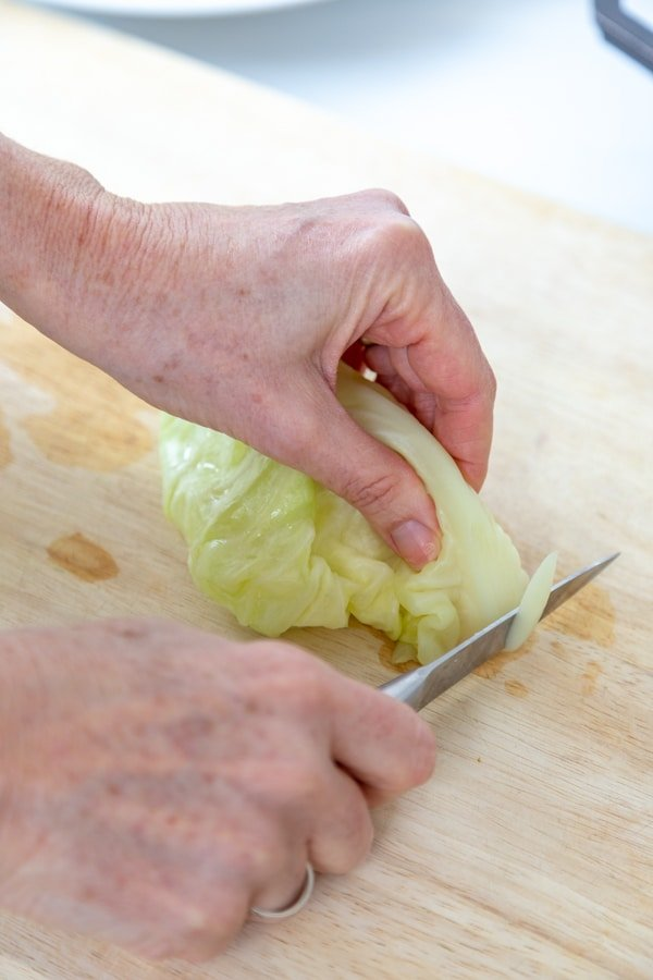 A hand holding a cabbage leaf and cutting the hard stem off of the leaf with a knife.