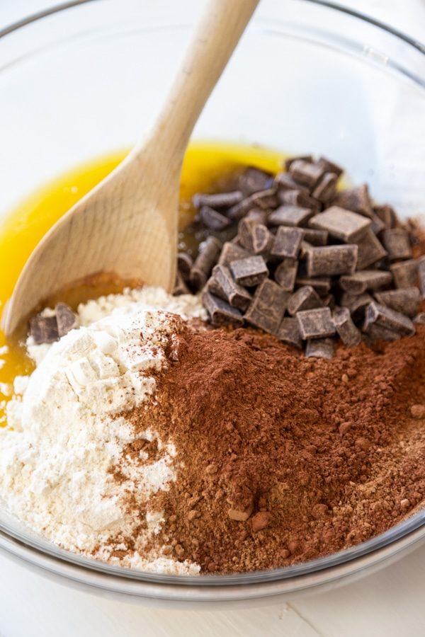 A glass mixing bowl with flour, cocoa powder, melted butter, and chocolate chunks and a wooden spoon.