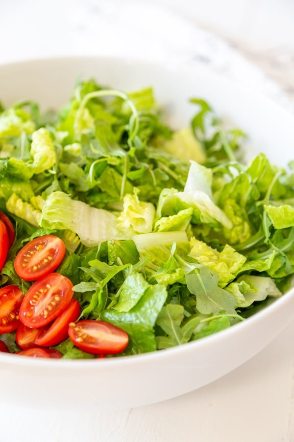 A white bowl with chopped lettuce and sliced cherry tomatoes.