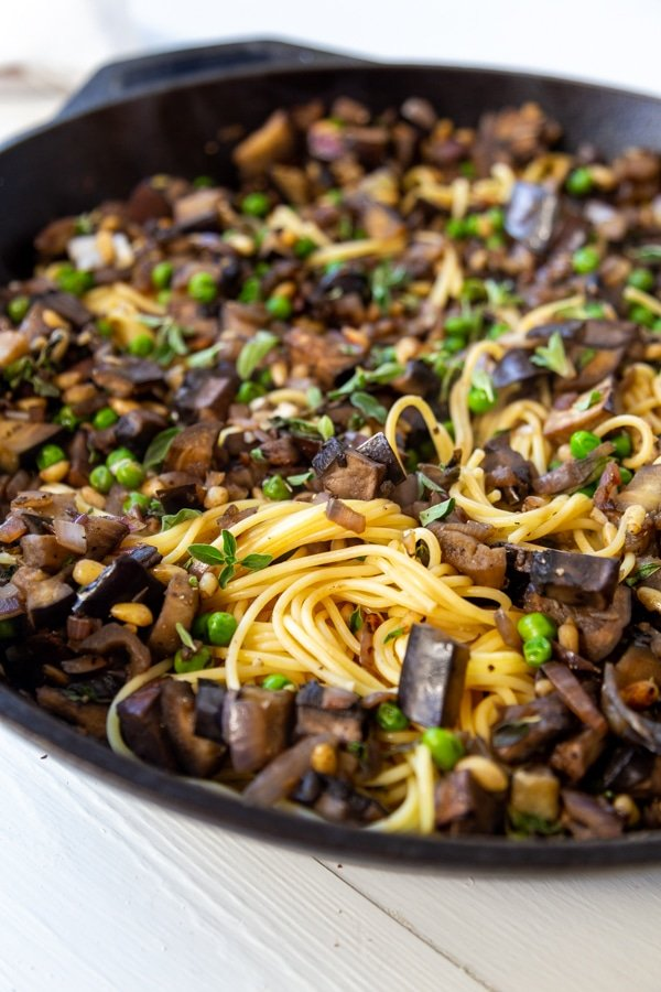 An iron skillet filled with spaghetti and eggplant and peas.