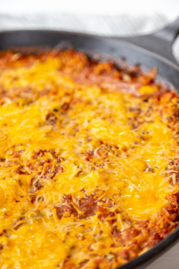 A cast iron skillet with a casserole topped with melted cheese.