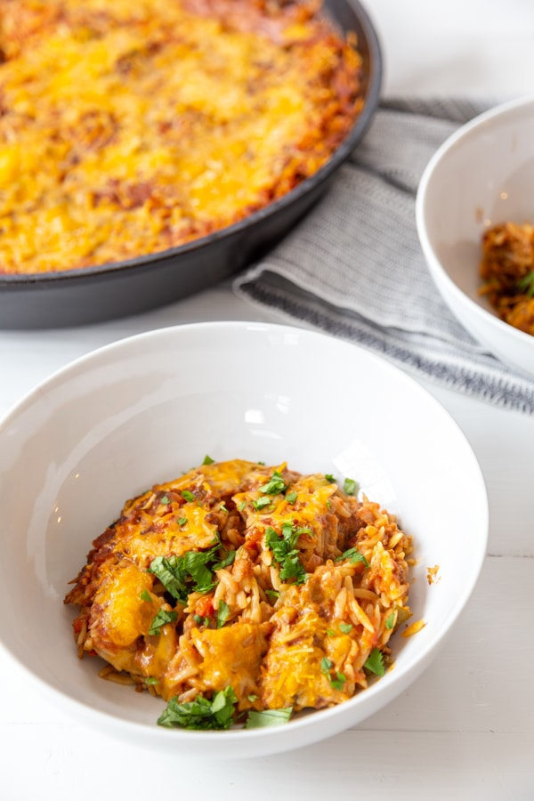 2 white bowls filled with Mexican casserole and the casserole in the background.