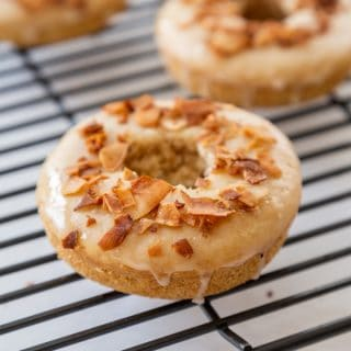 Doughnuts with coconut bacon chips on top cooling on a wire rack.