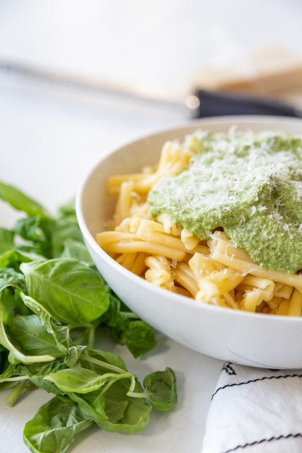 A white bowl with pasta and topped with pesto and basil leaves next to the bowl.