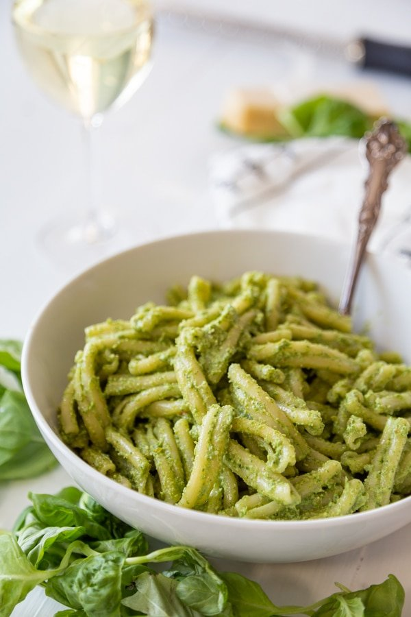 A white bowl with pasta and pesto with a silver fork in the bowl and basil leaves around it.