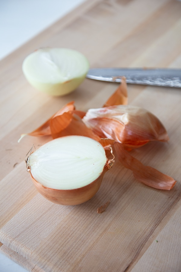 A cutting board with an onion cut in half.