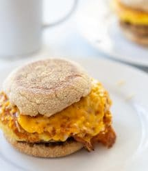 An egg and sausage breakfast sandwich on a white plate with a white coffee cup behind the plate.