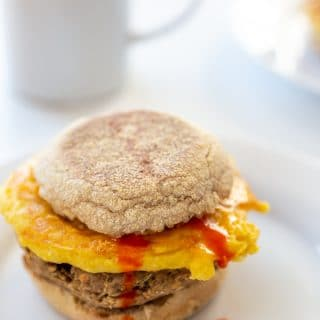 A sausage, egg, and cheese breakfast sandwich with hot sauce dripping down the sandwich.