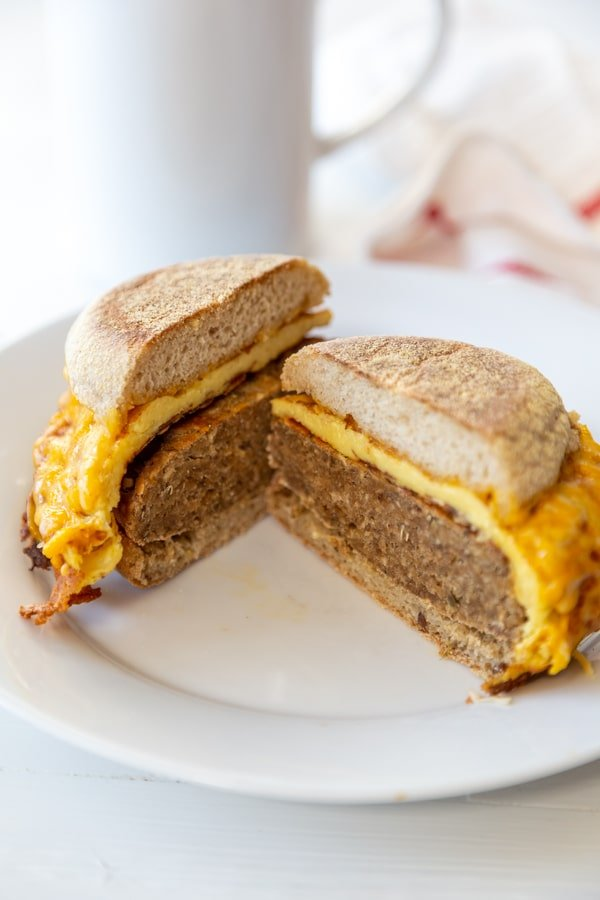 A sausage and egg breakfast sandwich cut in half on a white plate with a white coffee cup in the background.