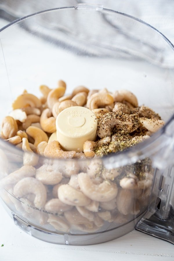 A food processor with cashews and spices.