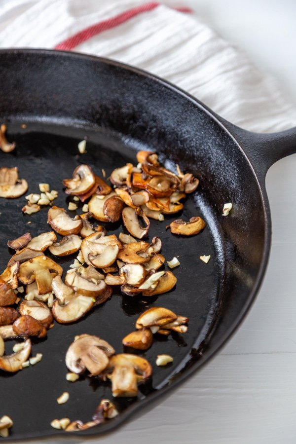 An iron skillet with cooked sliced mushrooms and garlic.