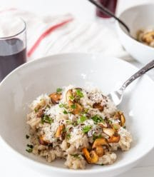 A white bowl with mushroom risotto with a fork in the bowl and a glass of wine and a white and red towel in the background.