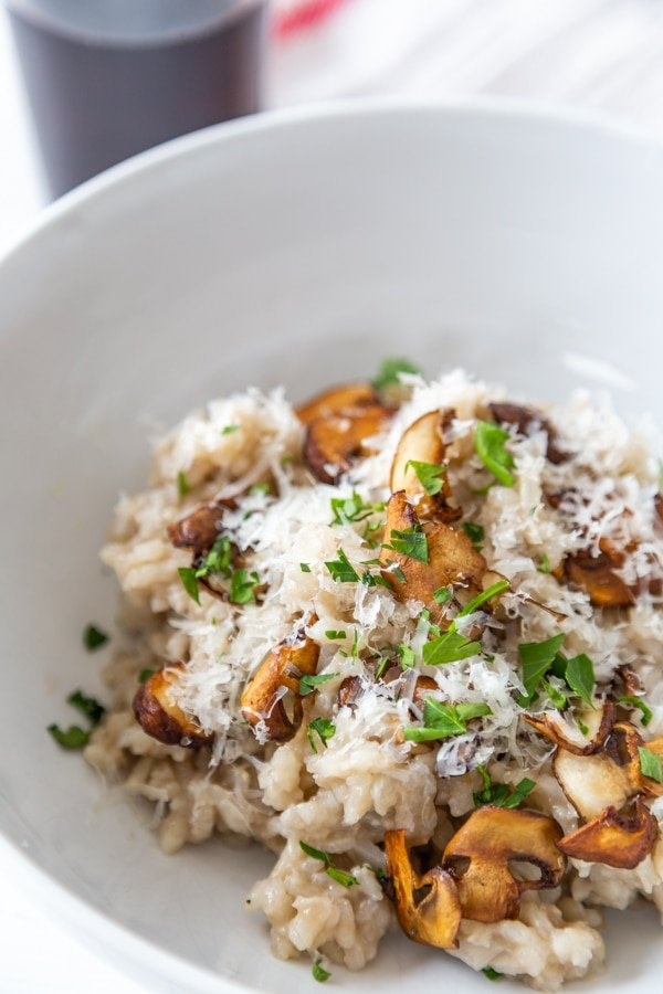 A close up shot of mushroom risotto with chopped basil and grated parmesan cheese on top.