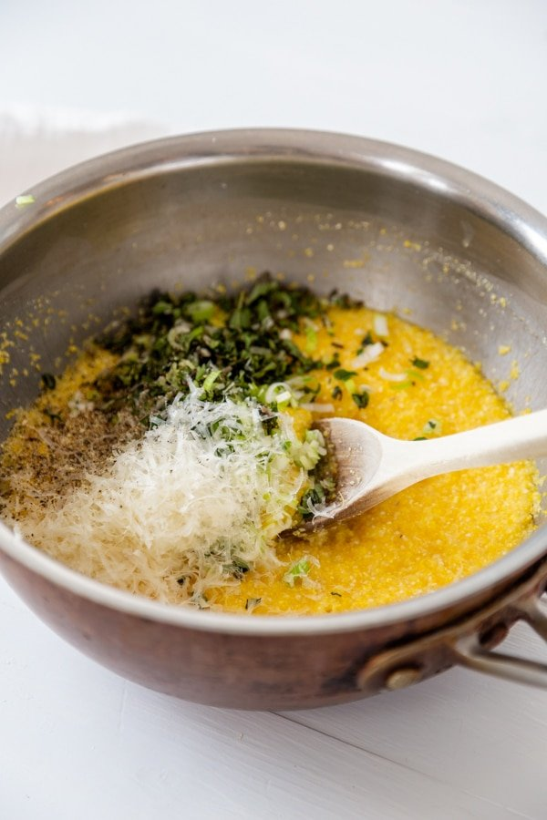 A copper saucepan with polenta and chopped herbs and grated parmesan with a wooden spoon.