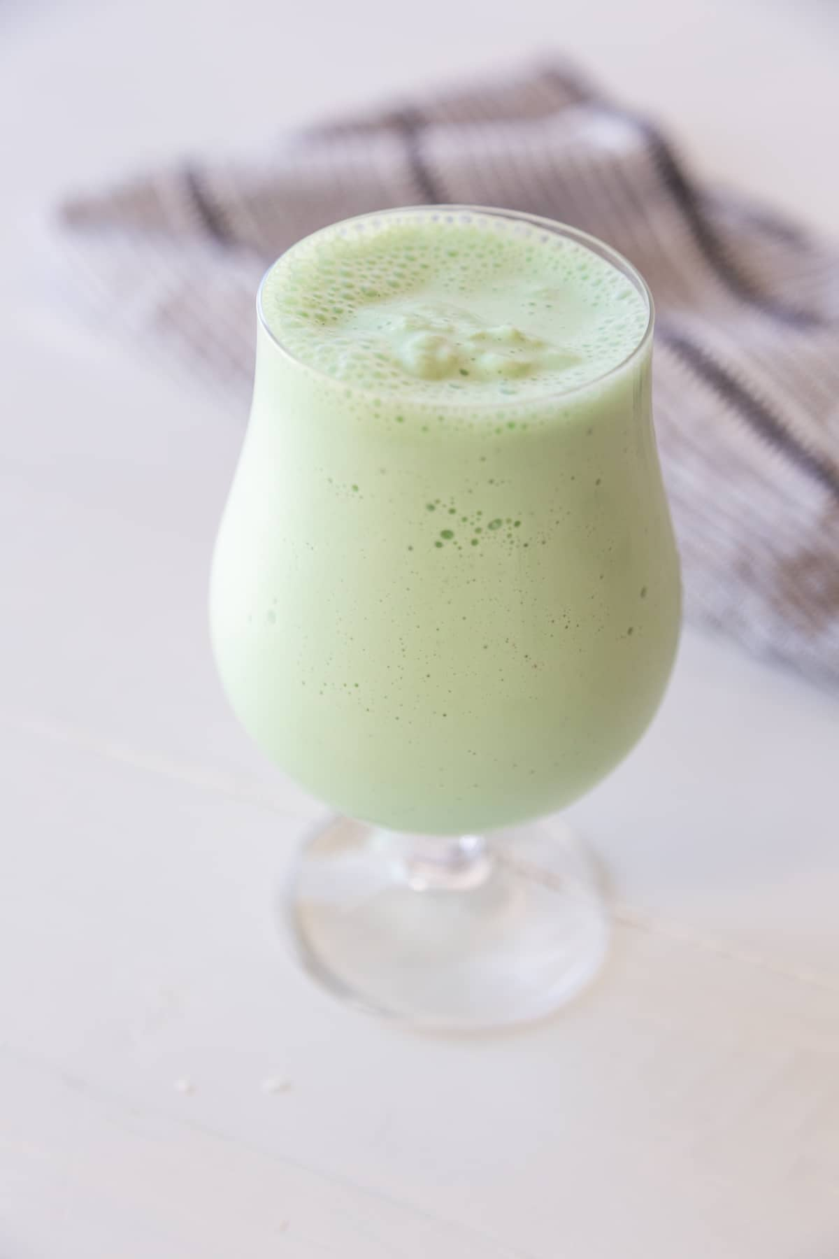 A green milkshake in a glass with a white and black towel behind the glass.