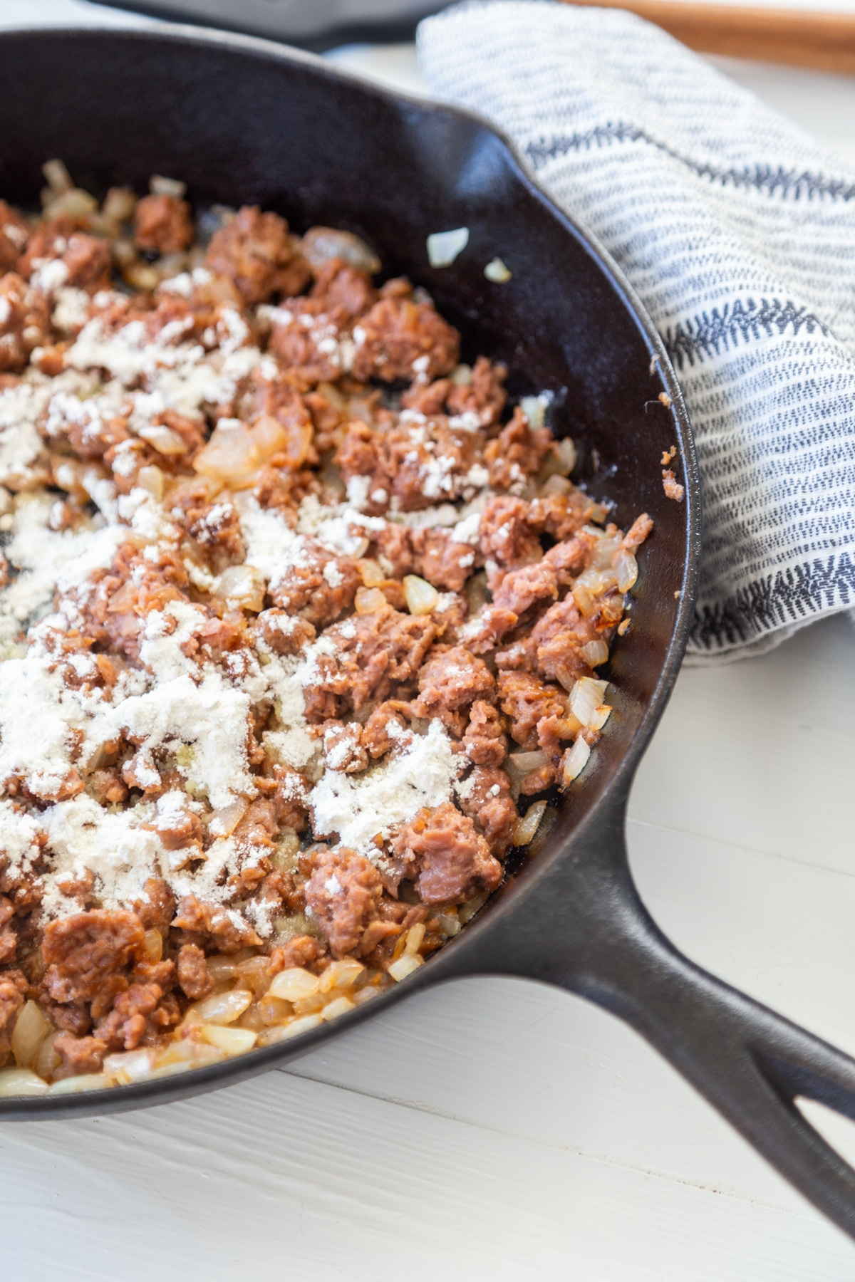 An iron skillet with ground beef and flour sprinkled on top of the meat.