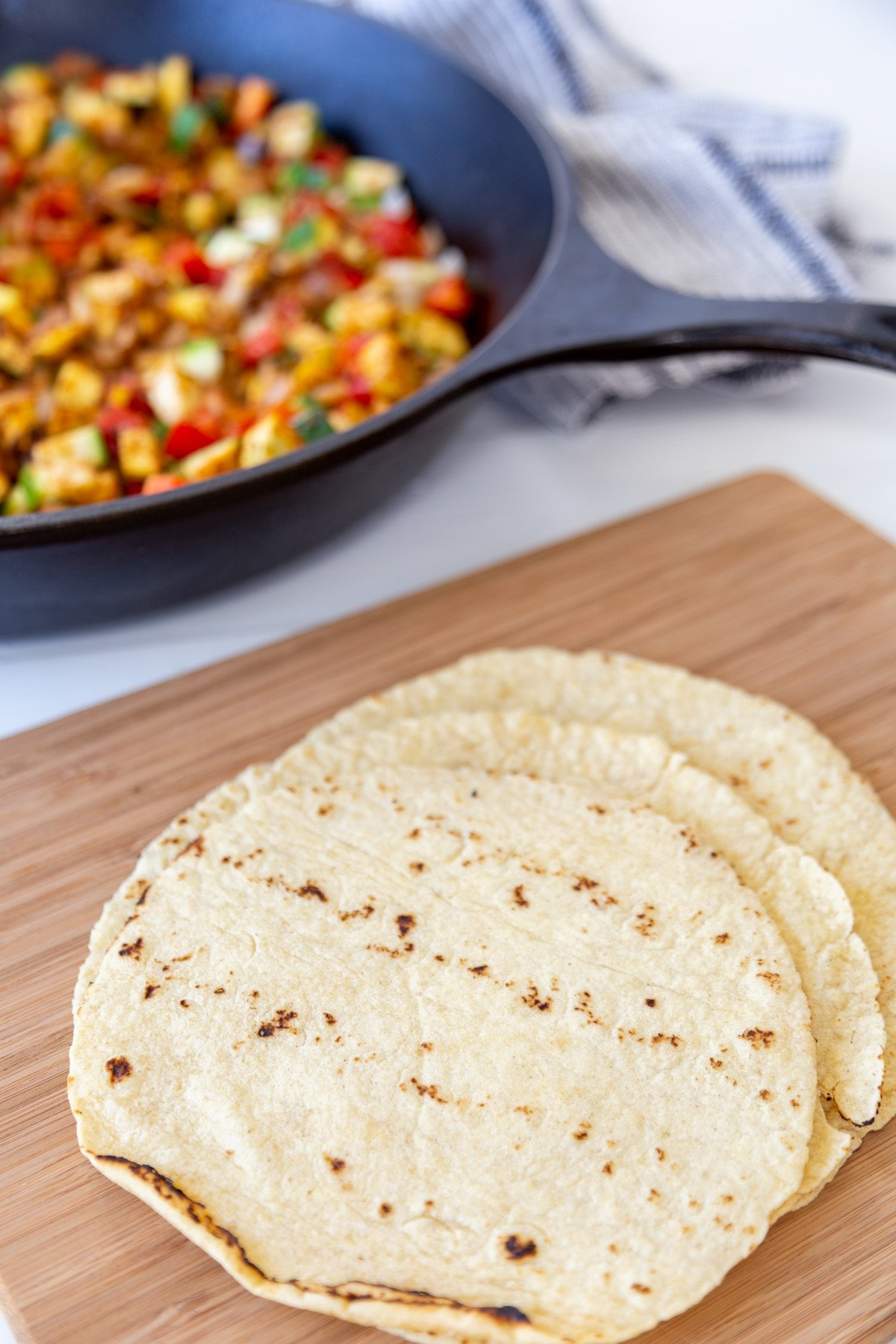 A stack of flour tortillas on a wood board with a skillet of diced veggies behind it.
