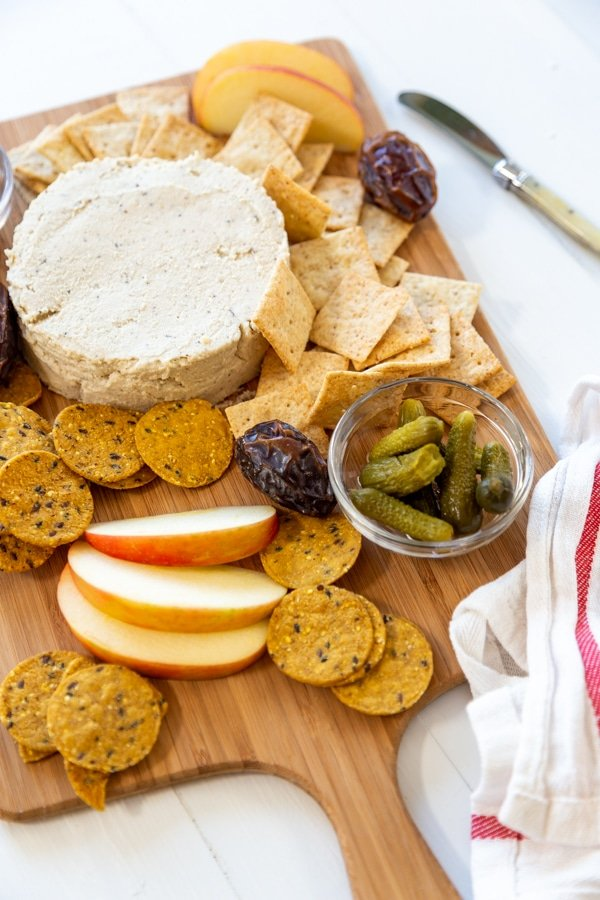 A cheese board with cheese, apples, crackers, and pickles.