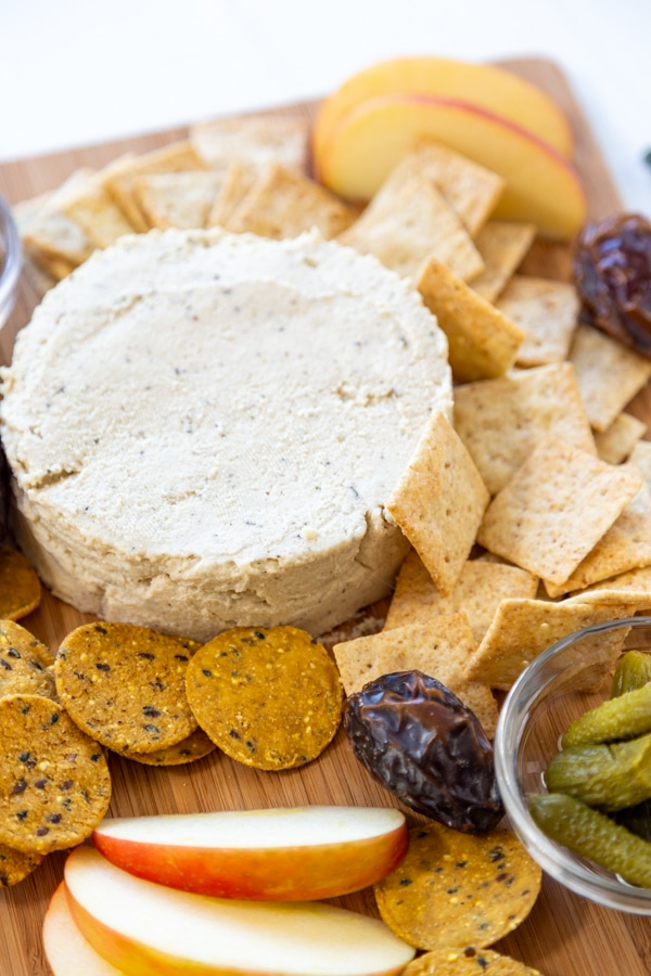 A cheese board with a round piece of spreadable cheese, crackers, and fruit.