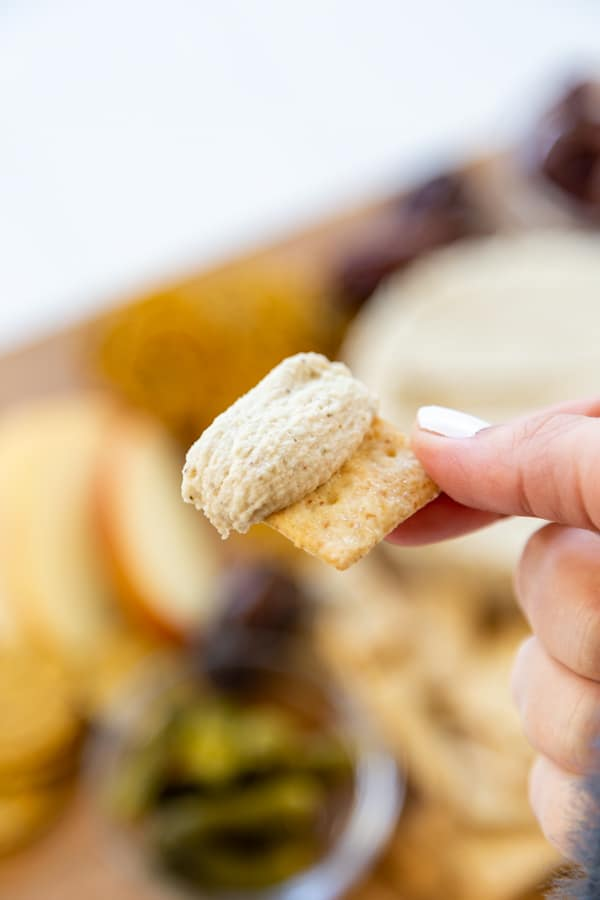 A hand holding a cracker with spreadable cheese over a cheese board.