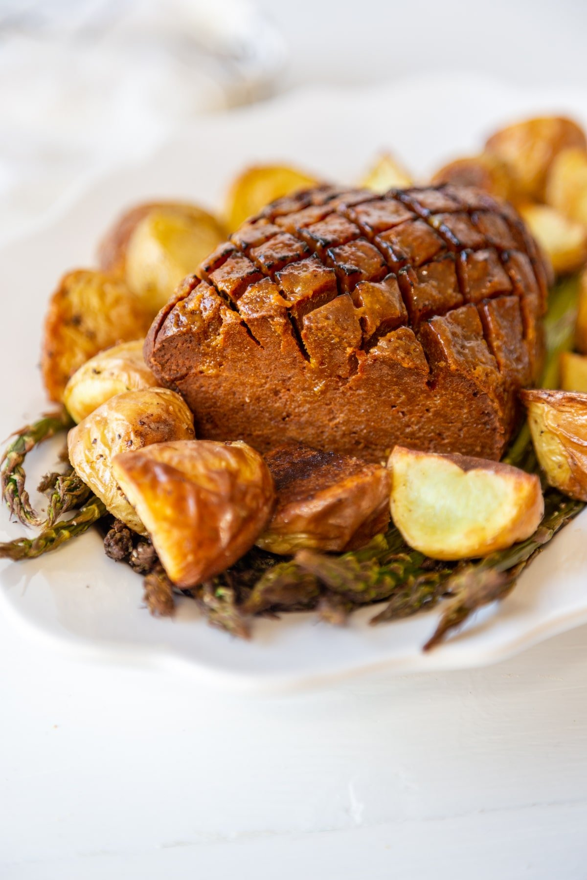 A vegan ham on a white platter with roasted asparagus and potatoes.