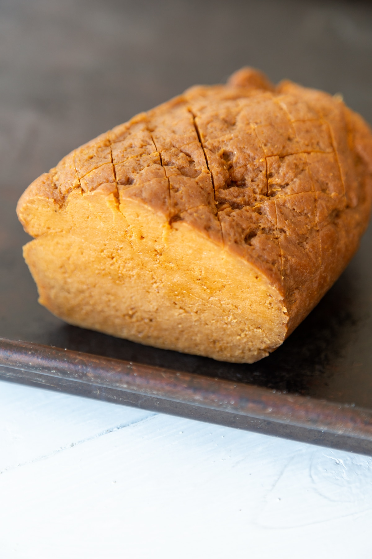 A seitan ham roast with a slice cut from the end of it.