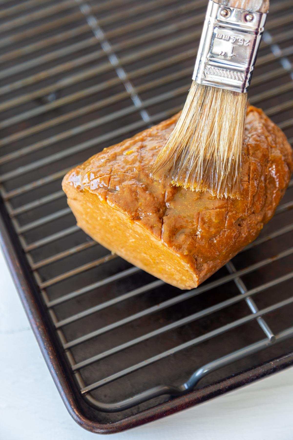 A pastry brush glazing a vegan ham.